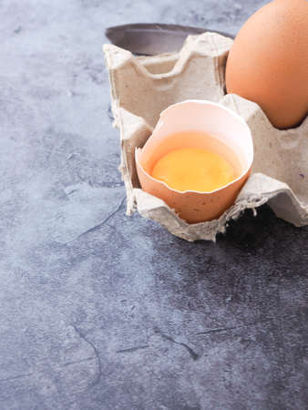 Fresh egg half-cracked with yolk in a brown paper tray on a grey background. Concept food of healthy. Banque d'images
