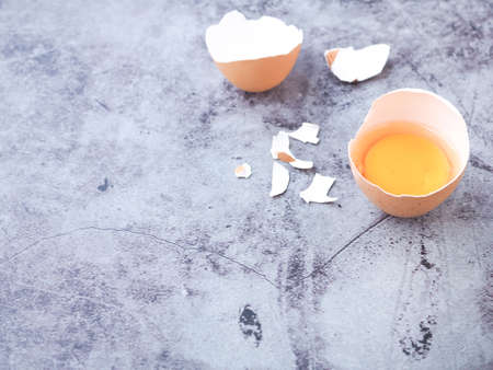 Fresh egg half-cracked with yolk on grey background. High protein and Vitamin foods. Concept food of healthy.