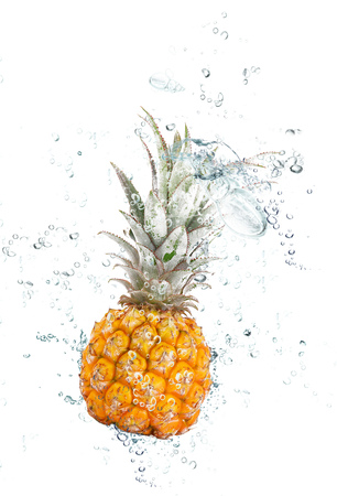 fresh pineapple falling in water