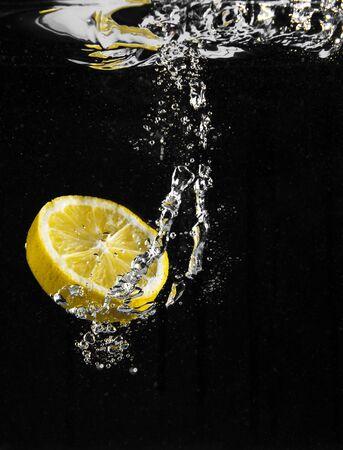 fresh lemon falling in water Stock Photo