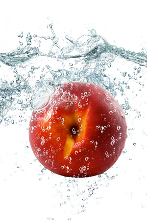 fresh peach falling in water Stock Photo