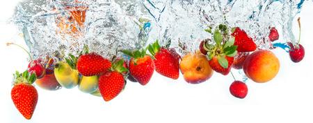 frische Früchte fallen ins Wasser