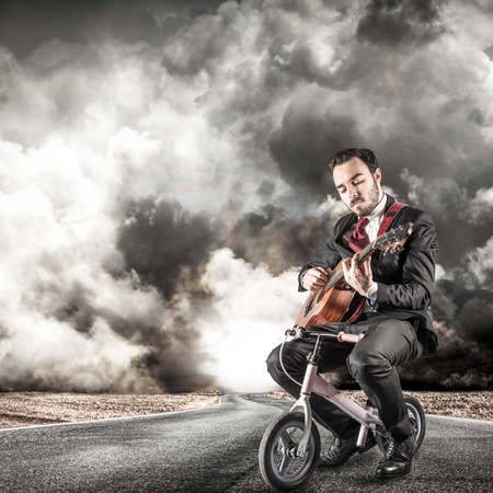 street musician: young manager play a classic guitar on a little bike