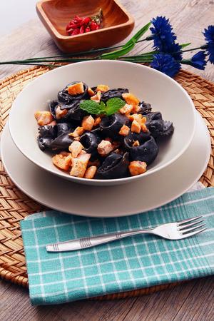 black ravioli at squid ink with salmon Stock Photo