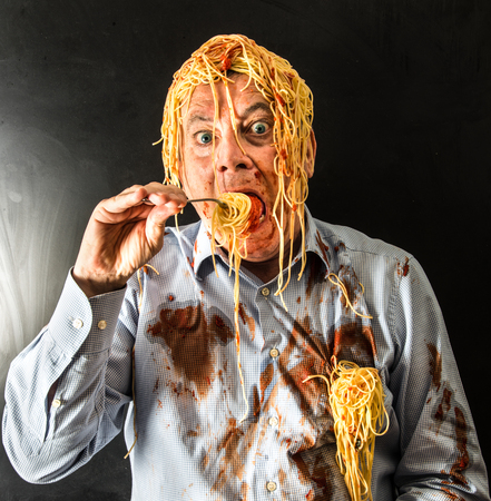 mad man eating spaghetti with tomato sauce in head