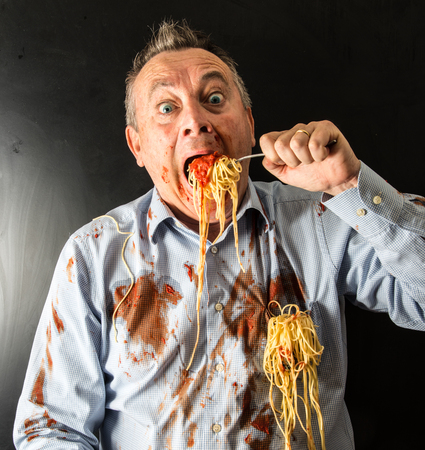 mad man eating spaghetti with tomato sauce