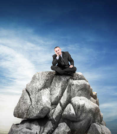 manager sitting on a big rock