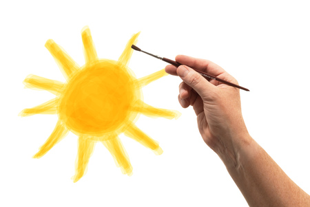 hand with brush drawing a sun on paper Stock Photo