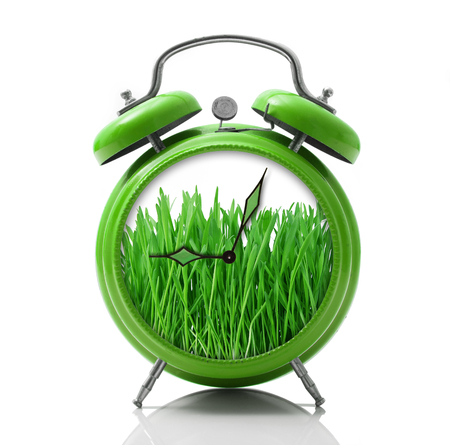 isolated alarm clock with grass dial on white background Stock Photo