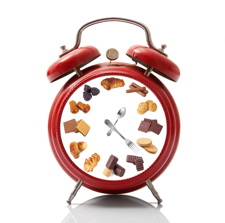 isolated alarm clock with cookies dial on white background Фото со стока