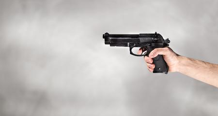 hand with gun on grey background