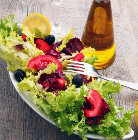 salad with tomatoes and olive on old wooden table