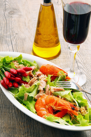 salad with shrimp and tuna on old wooden table