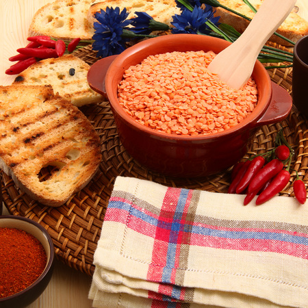 dry orange lentils in rustic dish on wooden table