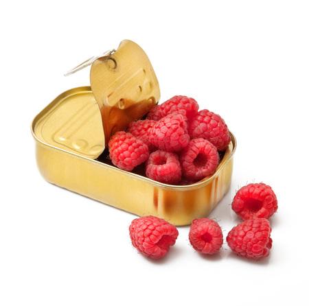 fresh raspberries in tin box on white background