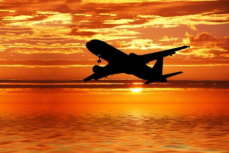 an airplane flying over a sea sunset Stock Photo