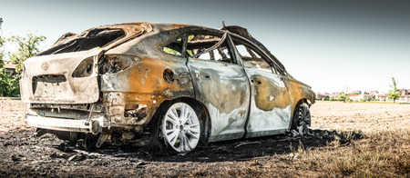 abandoned burnt car in isolated field Stock Photo