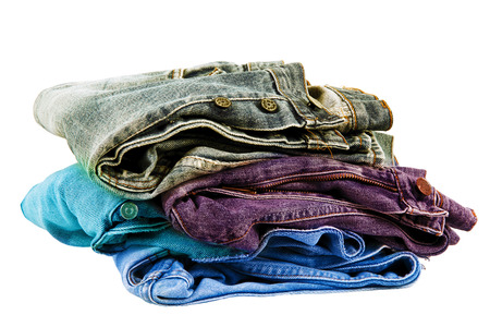 Jeans pants stacked on white background Stock Photo