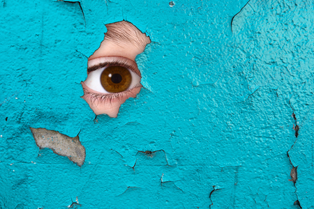 an Eye spying through a wall Stock Photo