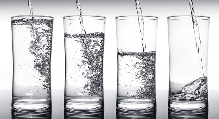 Water filling four glasses in sequence Stock Photo