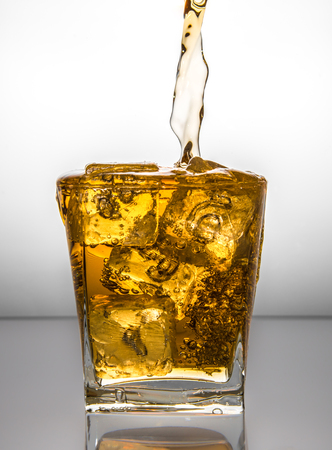 a glass with ice and liquid splash