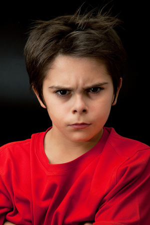 angry young boy on dark background
