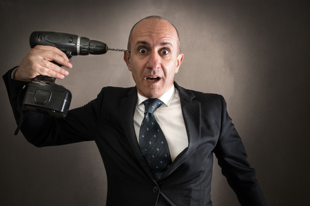Businessman pointing a drill to the head