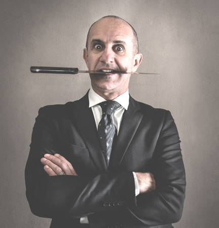 Aggressive manager with knife between teeth