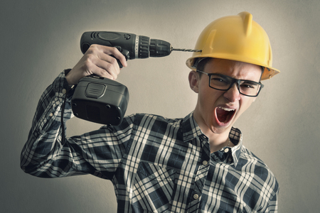Young construction worker simulates shooting himself with a drill