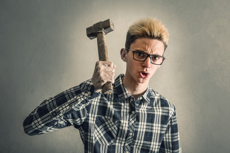Aggressive boy threatening with a hammer Stock Photo