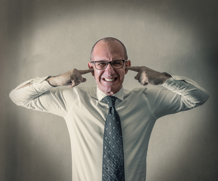 a Stressed manager with his fingers in his ears Stock Photo
