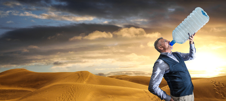 a Desert panorama of the dunes at sunset with man drinking
