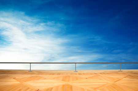 a Wooden floor with metal balustrade and blue sky
