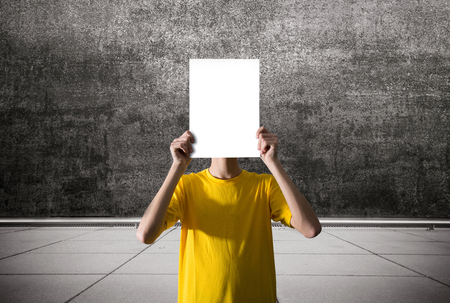 a person holding a blank sheet of paper Фото со стока