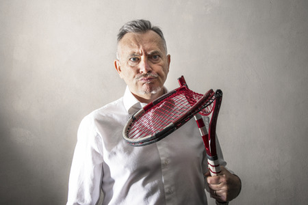 a discouraged man watching his broken tennis racket