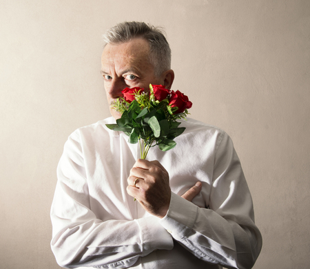 a man holding a bunch of flowers in his hand