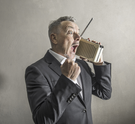 a Businessman listening to the radio making strange expressions