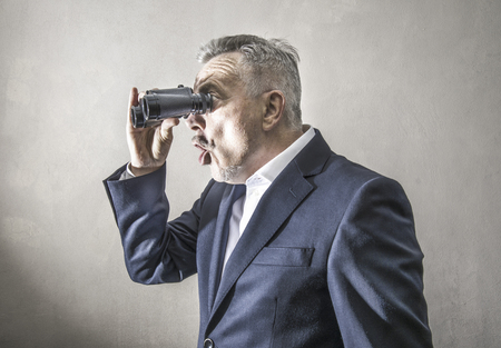 a Businessman looking with a binoculars