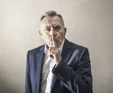 a Man imposes silence in an arrogant way Stock Photo