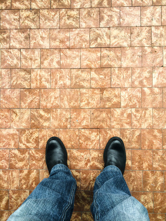 standing on a floor of brown tiles