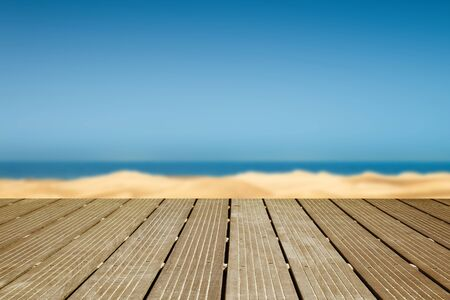 a wooden walkway with a view of the dunes and the sea Standard-Bild