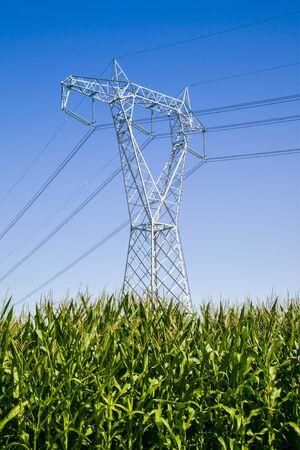 a high voltage pylon in a cultivated field Фото со стока