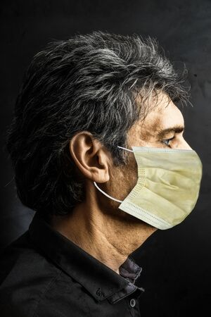 Portrait of Caucasian man in profile with surgical mask