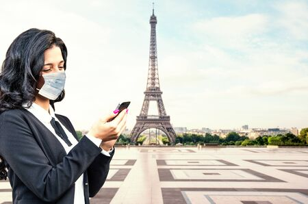 beautiful girl with smartphone and surgical mask near Eiffel Tower in Paris