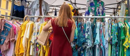 a woman looking at clothes at the market Archivio Fotografico