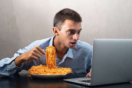 a man eating spaghetti with tomato sauce and watching the computer