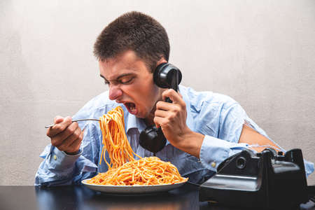 a boy eating spaghetti with tomato sauce and speaking at phone Archivio Fotografico
