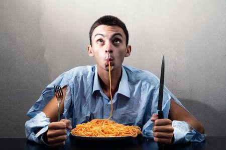 a man eating spaghetti with tomato sauce