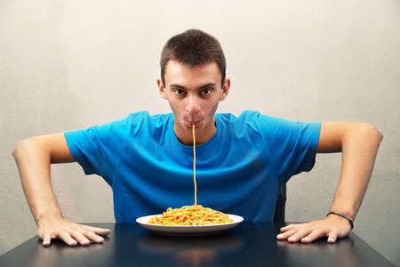an young man eating spaghetti with tomato sauce Archivio Fotografico