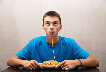an young man eating spaghetti with tomato sauce 免版税图像